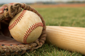 Baseball in glove with a bat