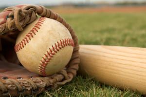 Baseball in glove with a bat